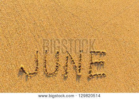 June - word inscription on the gold sand sea beach.