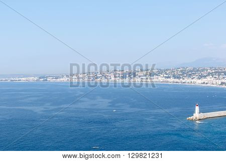Wide angle view of blue water harbor of Nice, France, with lighthouse on quay