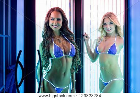 Pretty smiling girls posing in modern tanning booth