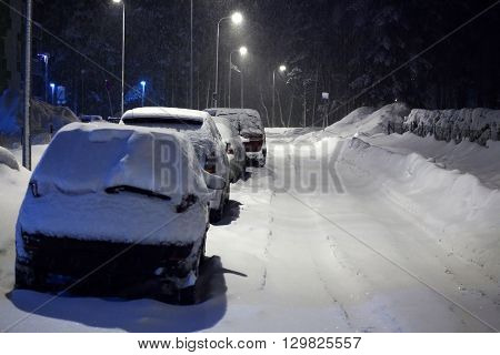 Cars under snow at night time by winter road