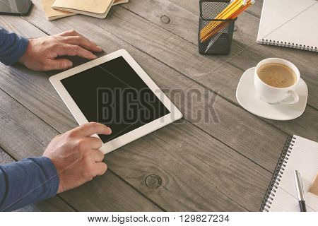 Man working in a home office. Men hand clicks on the tablet screen on wooden table. concept man working from home using tablet computer or working outside the office