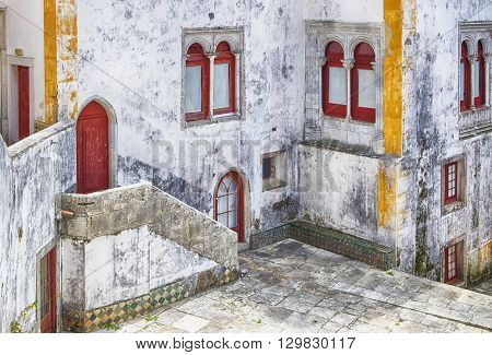 A small interior courtyard of one of the historic buildings in Sintra Portugal is a quiet spot to reflect on elements of the Moorish influence on the architeture. The building shows some signs of direpair with craked walls and faded paint.