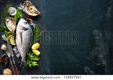 Delicious fresh fish and oysters with aromatic herbs, spices and vegetables on dark slate plate