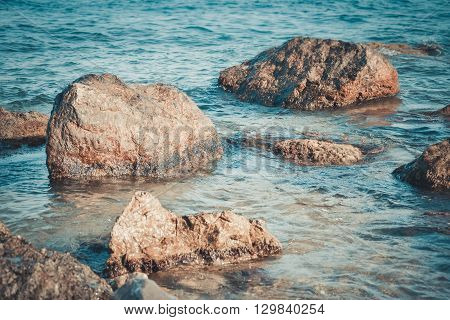 stones on the beach in the clear water the filter