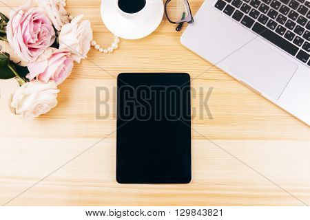 Top view of woman's workplace with blank tablet flowers coffee and keyboard. Mock up