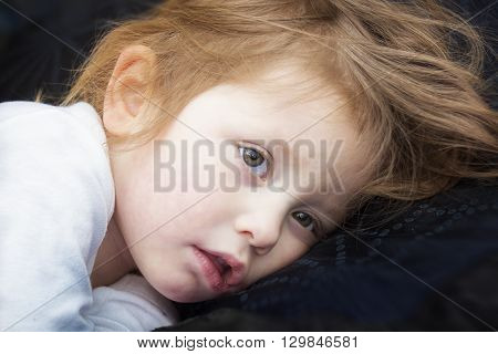 Portrait of a sick little girl in a bed