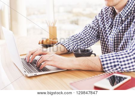 Male hands using laptop on wooden desk with coffee croissant smartphone and notepads