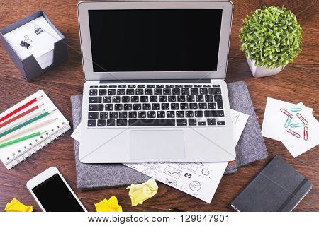 Blank laptop on creative office desktop. Freelance desktop with accessories and distant work tools blank laptop computer smartphone and stationery items. Business workspace in home or office poster