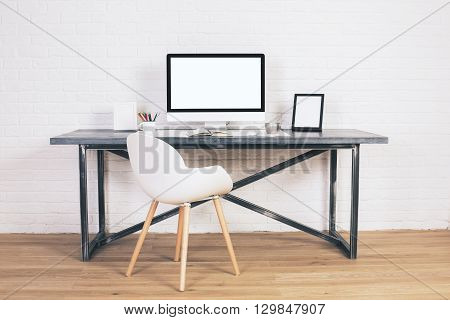 Front view of modern chair and designer desk with blank white computer screen and picture frames on white brick background. Mock up