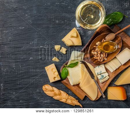 Various types of cheese  on wooden tray with white wine on black background, top view