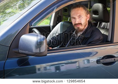 Bearded serious Asian man with keys as a driver of modern Japanese suv outdoor portrait in open car window