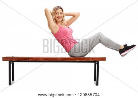 Female athlete doing abdominal crunches on a bench and looking at the camera isolated on white background