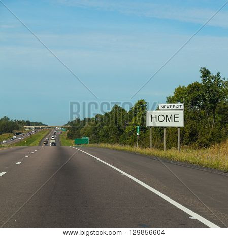 Sign at the side of a road with HOME NEXT EXIT on it