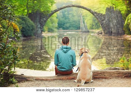 Pensive young man sitting on the pond bank with a his dog - Amazing place in Germany. Rakotzbrucke also known as Devils Bridge in Kromlau.