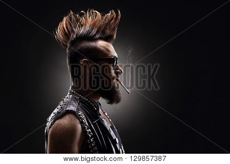 Profile shot of a punk rocker smoking a cigarette on dark background