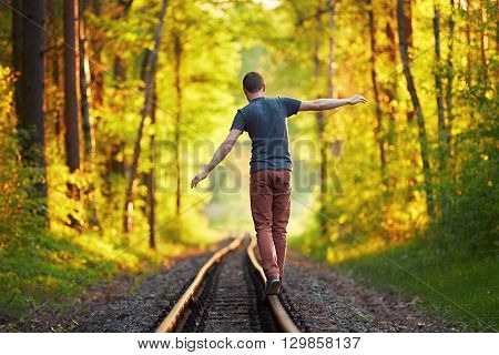 Summer time - Young man enjoying on the trip. Walk on the railroad track in forest at the sunset.