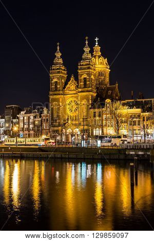 AMSTERDAM NETHERLANDS - 16TH FEBRUARY 2016: A view towards the Church of Saint Nicholas in Amsterdam at night. Reflections can be seen in the water.