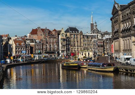 AMSTERDAM NETHERLANDS - 16TH FEBRUARY 2016: A view along the Rokin Canal in Amsterdam during the day. Allard Pierson Museum boats Building and people can be seen.