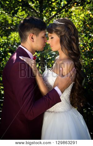 couple in wedding attire against the backdrop of the garden at sunset, the bride and groom