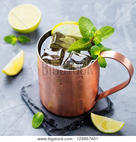 Cold Moscow Mules cocktail with ginger beer, vodka, lime Grey stone background