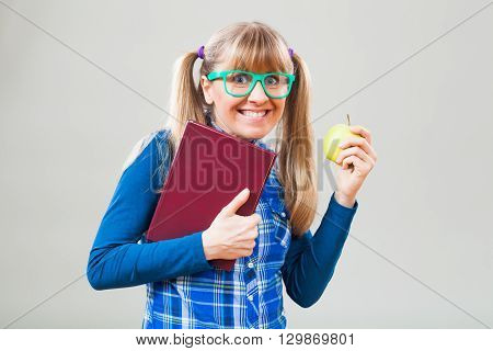 Studio shot portrait of nerdy student girl who is holding book and apple