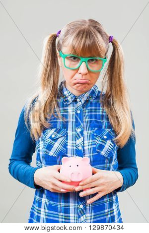 Studio shot portrait of sad nerdy woman who is holding empty piggy bang.