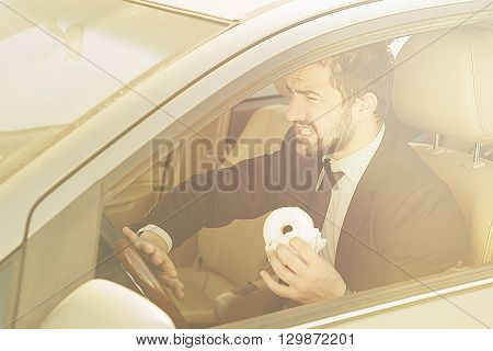Toned picture of businessman holding doughnut while driving car. Busy man hurrying to office and eating on to go.