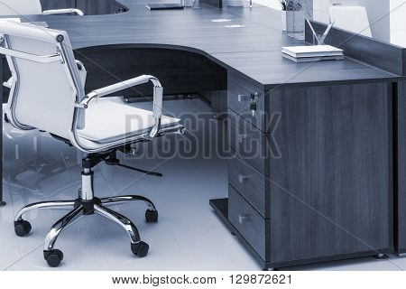 desks and white leather armchairs in the office