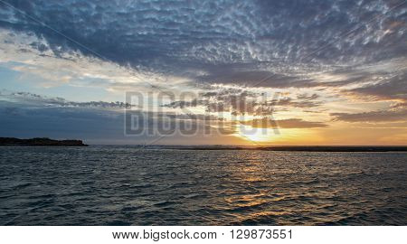 Calm waters and sunset skies over the Murchison River and river mouth waters in Kalbarri, Western Australia.
