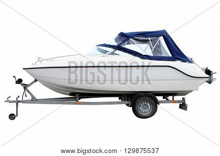 White motor boat with a blue awning loaded on a trailer for transportation.