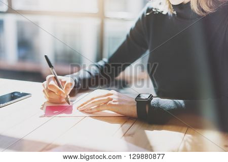 Photo Woman Working Modern Studio, Wearing Generic Design Smart Watch.Female Hands Writing Notes Document.Account Manager Work Process.Smartphone on Wood Table.Horizontal, Burred Background.Film effect.
