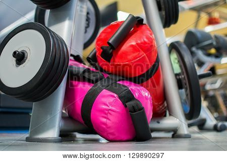 Fitness weights and sandbags, stowed on a rack.