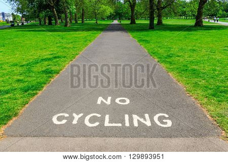 """""""No Cycling"""" warning written with white paint on tarmac pavement with visible tree and grass at the background"""