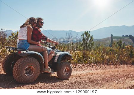 Couple In Nature On A Quad Bike