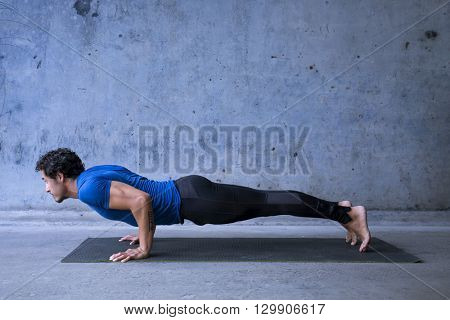 Young man practicing yoga. Basic yoga pose: chaturanga dandasana.