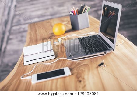 Side view of designer table with laptop smartphone office tools and orange