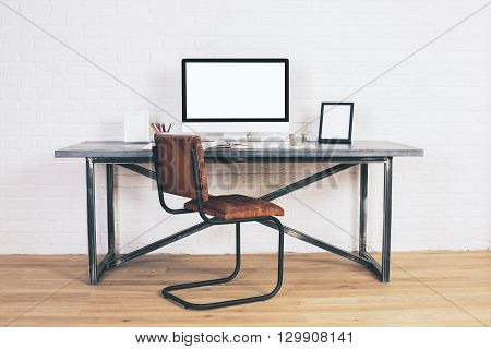 Front view of designer desk with empty computer display frames and other items with brown chair next to it. Wooden floor and white brick wall background. Mock up