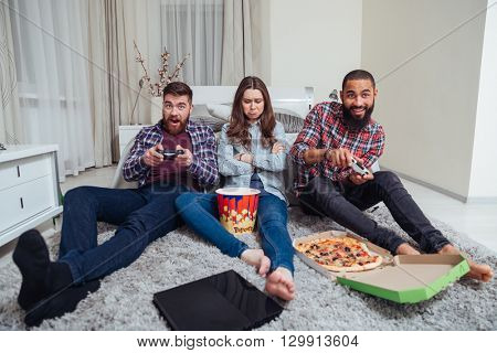Two happy young men playing computer games and sad offended young woman sitting in the room