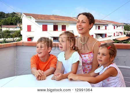 Mother and three children sit in  day-time on  balcony near  table and laugh