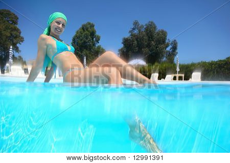 Woman in  swimming suit sits in  day-time in  pool  and put  leg into water