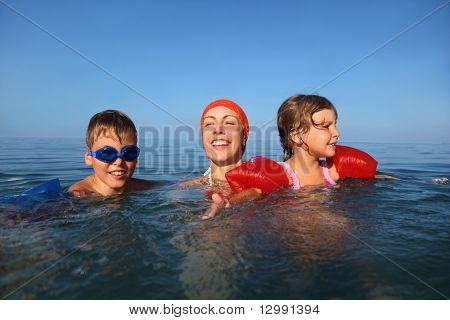 Mother in summer teaches to swim two children boy and girl  seaside, underwater package shot