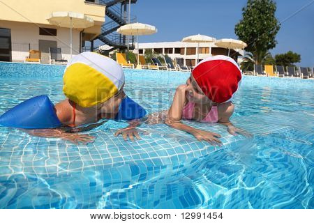 Two girls bath in  pool near skirting in  day-time on rest in  hotel