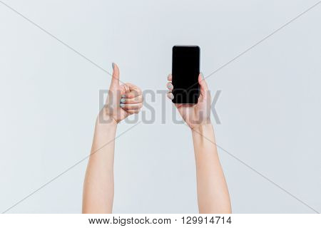 Female hands holding smartphone with blank screen and showing thumb up isolated on a white background