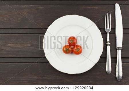 Very strict diet. Dietary vegetable diet. Tomatoes on a plate. Slimming diet. White plate with tomato on dark table.