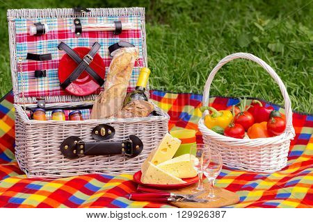 Picnic on the grass. Picnic basket with vegetables and bread. A bottle of wine with glasses and cheese.