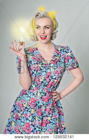 Cute blonde girl holding glowing light bulb - humorous concept