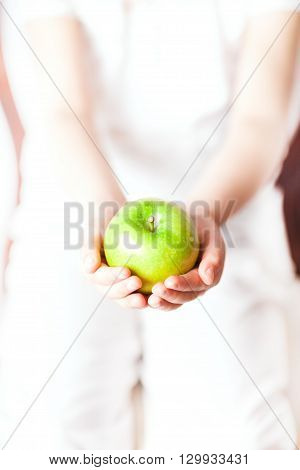 Young child is giving or receiving an apple.