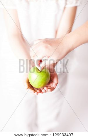 Mother is giving child a green apple.