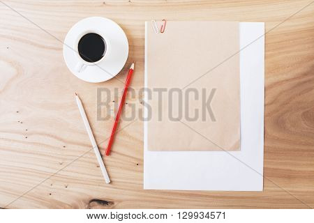 Top view of wooden desktop with blank brown and white paper sheets clipped together coffee cup and pencils. Mock up