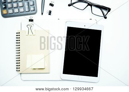 Blank tablet screen notepad and other tools on white office desk. Topview Mock up